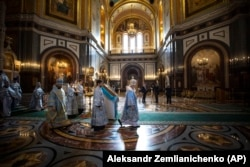 Russian Orthodox Church Patriarch Kirill (center) walks to conduct a religious service on the eve of Orthodox Easter during a live broadcast from an almost-empty cathedral in Moscow on April 17.