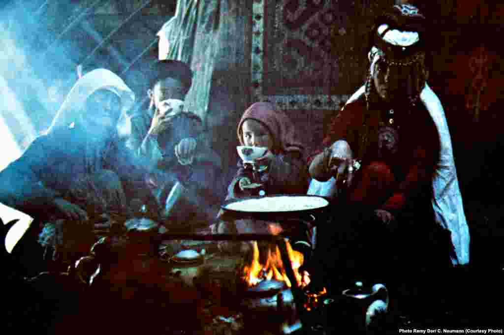 An archival photo of a nomadic family gathered around the fire