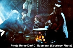 A nomadic Pamir Kyrgyz family gathers around an open-fire stove inside their yurt.