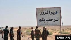 Солдаты сирийской армии у плаката с надписью «Добро пожаловать в провинцию Дейр-эз-Зор», 3 сентября 2017 г.
