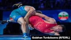 Атабек Азисбеков (в красном трико) в схватке за бронзовую медаль Чемпионата мира с узбекистанским борцом Рустамом Ассакаловым. Нур-Султан, 16 сентября 2019 года.