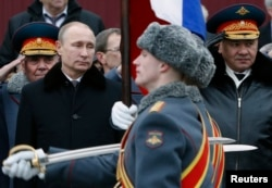 Russian President Vladimir Putin (left) and Defense Minister Sergei Shoigu (right) watch honor guards pass by as they attend a wreath-laying ceremony to mark the Defender of the Fatherland Day at the Tomb of the Unknown Soldier near the Kremlin on February 23.