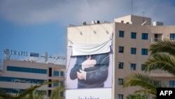 Постер сбежавшего Бен Али с опущенной верхней частью, 16 января 2011
