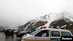 An ambulance on standby near the mountains where an Afghan Pamir Airways plane is thought to have crashed in the Salang pass on May 17.