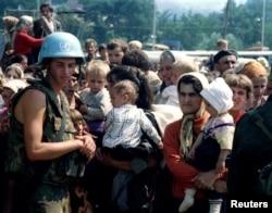 Soldat olandez al Națiunilor Unite și femeile refugiate care așteptau să plece din zona Srebeniței la începutul Genocidului.