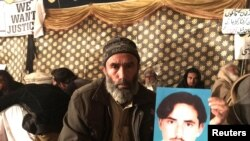 "Mohammad Bilal holds a picture of his son Hazratullah as he takes part in a protest with members of the Pashtun community against what they say are enforced ""disappearances"" and routine oppression, in Islamabad on February 8."