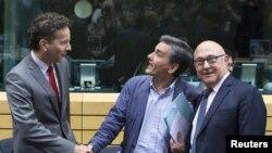 Новий міністр фінансів Греції Ефклідіс Цакалотос (с) на зустрічі голів мінфінів єврозони у Брюсселі 7 липня 2015 року; його вітають голова Єврогрупи Єрун Дейсселблум (л) і міністр фінансів Франції Мішель Сапен (р)