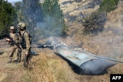 Pakistani soldiers stand next to what Pakistan says is the wreckage of an Indian fighter jet shot down in Pakistan-controlled Kashmir on February 27.