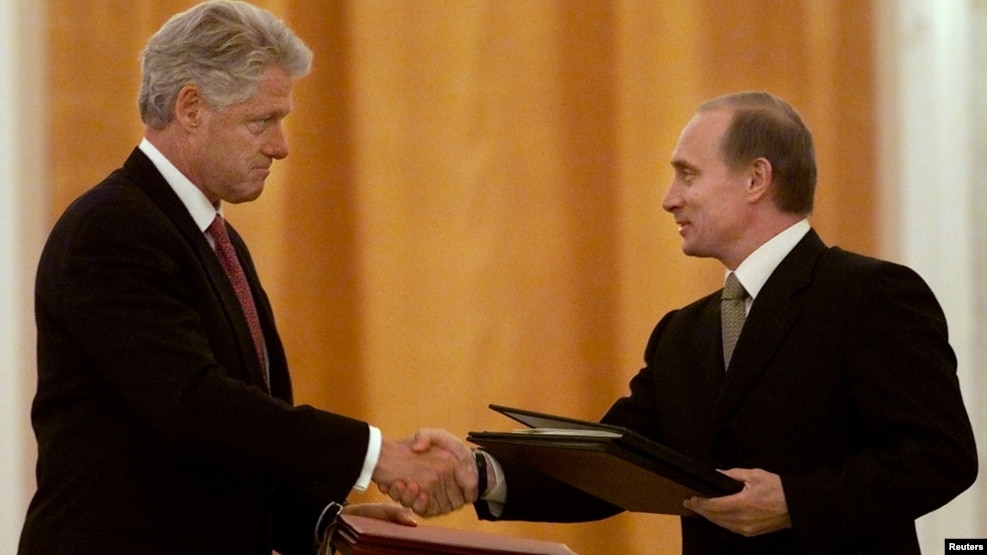 Russian President Vladimir Putin (right) and U.S. President Bill Clinton exchange agreements on the safe disposition of 68 metric tons of weapons-grade plutonium in Moscow on June 4, 2000.