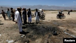 FILE: Afghan villagers stand at the site of an attack in Parwan Province in July.