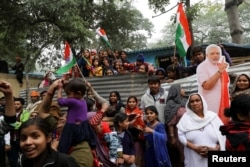 Hindu refugees from Pakistan's Sindh Province stand next to a cutout of Narendra Modi, India's Prime Minister, as they celebrate the Citizenship Amendment Bill being passed in India's Parliament.