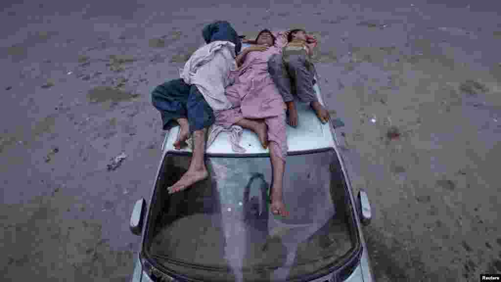 Pakistan - Djeca bez krova nad glavom usnula na autu, Karači, 22. august 2012. Foto: REUTERS / Akhtar Soomro