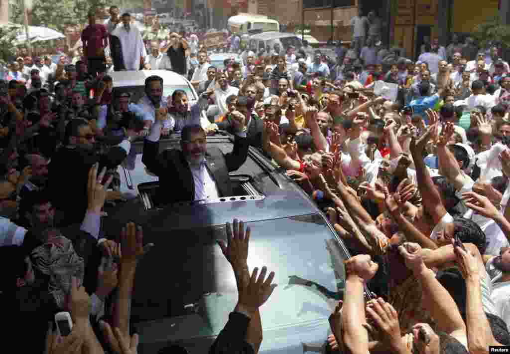 Egyptian presidential candidate Muhammad Morsi of the Muslim Brotherhood waves to a crowd outside a mosque after attending Friday Prayers in Cairo. (Reuters/Ahmed Jaddalah)