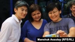 Жанар Секербаева (слева), Гульзада Сержан (справа), инициаторы создания Feminita, с адвокатом Айман Умаровой у здания административного суда. Алматы, 20 августа 2018 года.