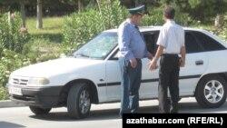 Aşgabadyň köçeleriniň birinde polisiýa işgäri we awtoulag sürüjisi.