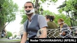 Грузинские печатные издания, помещенные в клетку, и человек, прикованный к ней наручниками, люди с белыми повязками, закрывающими глаза и рты
