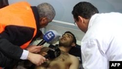 An Arab League observer speaks with a wounded man in a hospital after a powerful explosion in Damascus earlier this month.