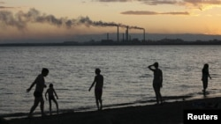 Residents walk the shore of Lake Balkhash at dusk, in front of the city's 1930s-built copper smelter owned by Kazakhmys copper mining company in the city of Balkhash.