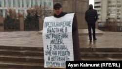 Гражданский активист Асхат Жексебаев у монумента Независимости на площади Республики проводит пикет в защиту политических заключенных. Алматы, 11 ноября 2019 года.