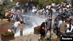 متظاهرون أتراك يتراجعون بعد أن أطلقت قوات مكافحة الشغب قنابل الغاز المسيل للدموع في أسطنبول>