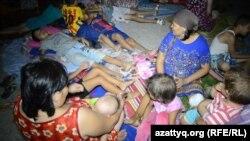 Женщины и дети спят во дворе здания общежития в Кызылорде. 5 августа 2015 года.