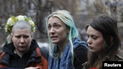 Activists from the Ukrainian women's rights group Femen hold an impromptu press conference on their return to Kyiv (from left to to right: Aleksandra Nemchinova, Inna Shevchenko, and Oksana Shachko).