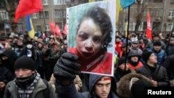 Митинг у здания МВД 25 декабря. В руке у одного из участников акции фотогорафия избитой Татьяны Чорновил