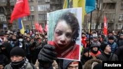 Учасник акції протесту під Міністерством внутрішніх справ тримає в руках фото жорстоко побитої Тетяни Чорновол, 25 грудня 2013 року