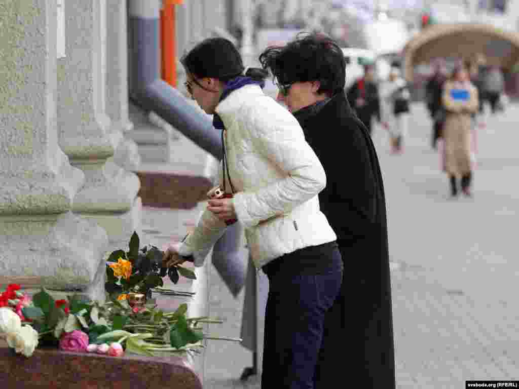 People place flowers in a makeshift memorial outside the subway station.