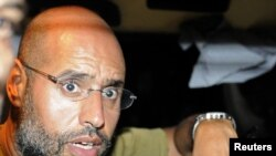 Saif al-Islam speaks to reporters in Tripoli on August 23.