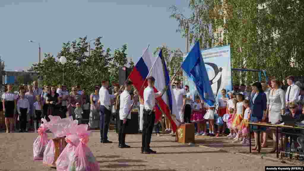 Старшокласники з прапорами гімназії, Криму та Росії