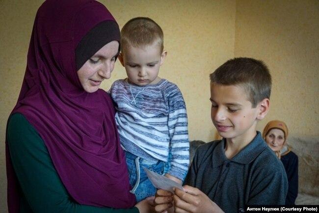 Эльзара Сулейманова держит на руках своего сына Мусу