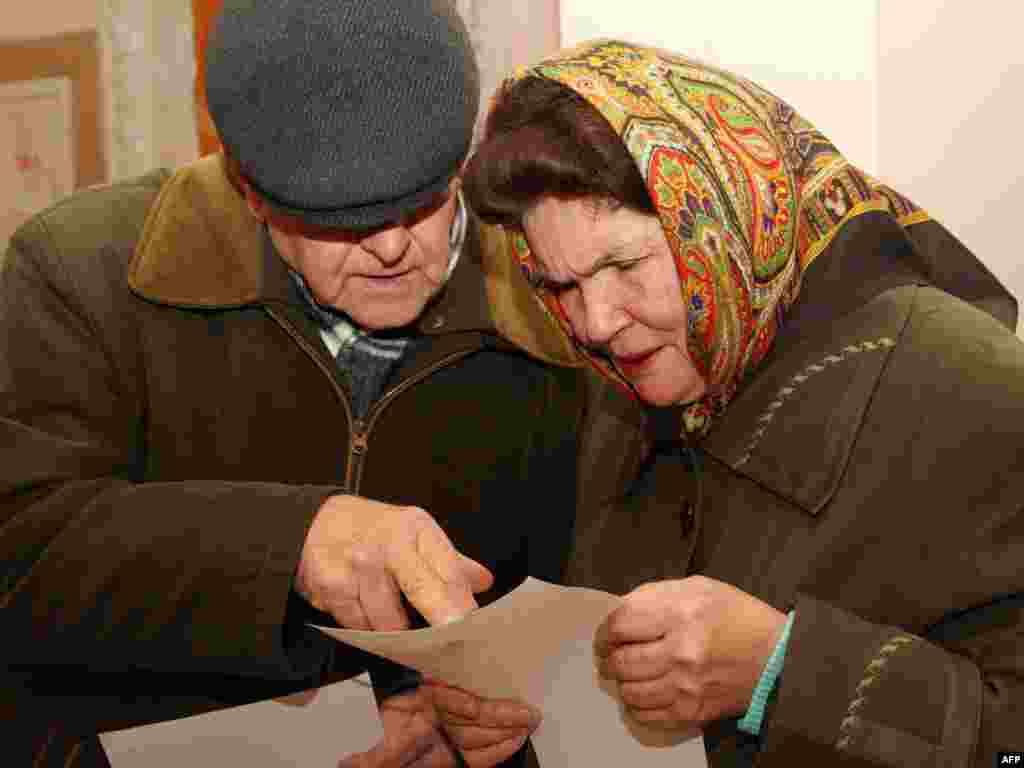 An elderly Ukrainian couple studies the ballot at a polling station in Chop, 800 kilometers west of Kyiv.