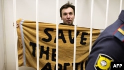 "Polish Greenpeace International activist Tomasz Dziemianczuk, who left Russia on December 29, displays a ""Save The Arctic"" banner made from a towel during his detention hearing in St. Petersburg in mid-November."