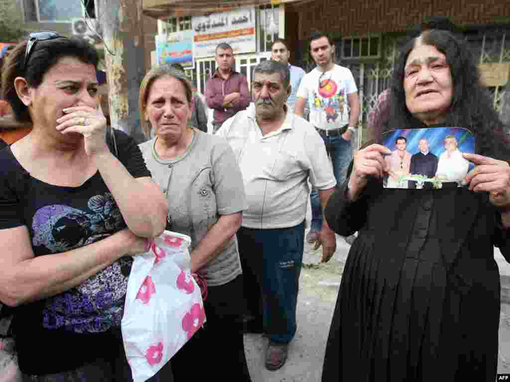 یک زن مسیحی در بغداد تصویر پسرش را که در جریان گروگانگیری کشته شده است در دست دارد- ۱۰ آبان - IRAQ, Baghdad : An Iraqi Christian woman (R) holds on November 1, 2010 a picture of her son (L) who was killed the night before along with 45 other Christians at the Sayidat al-Nejat Catholic Cathedral, or Syrian Catholic Church, in central Baghdad when US and Iraqi forces stormed the cathedral to free dozens of hostages in an attack claimed by Al-Qaeda gunmen. AFP PHOTO/AHMAD AL-RUBAYE