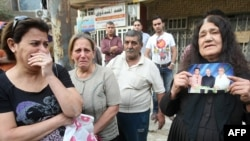 picture of her son (L) who was killed the night before along with 45 other Christians in central Baghdad, 01Nov2010
