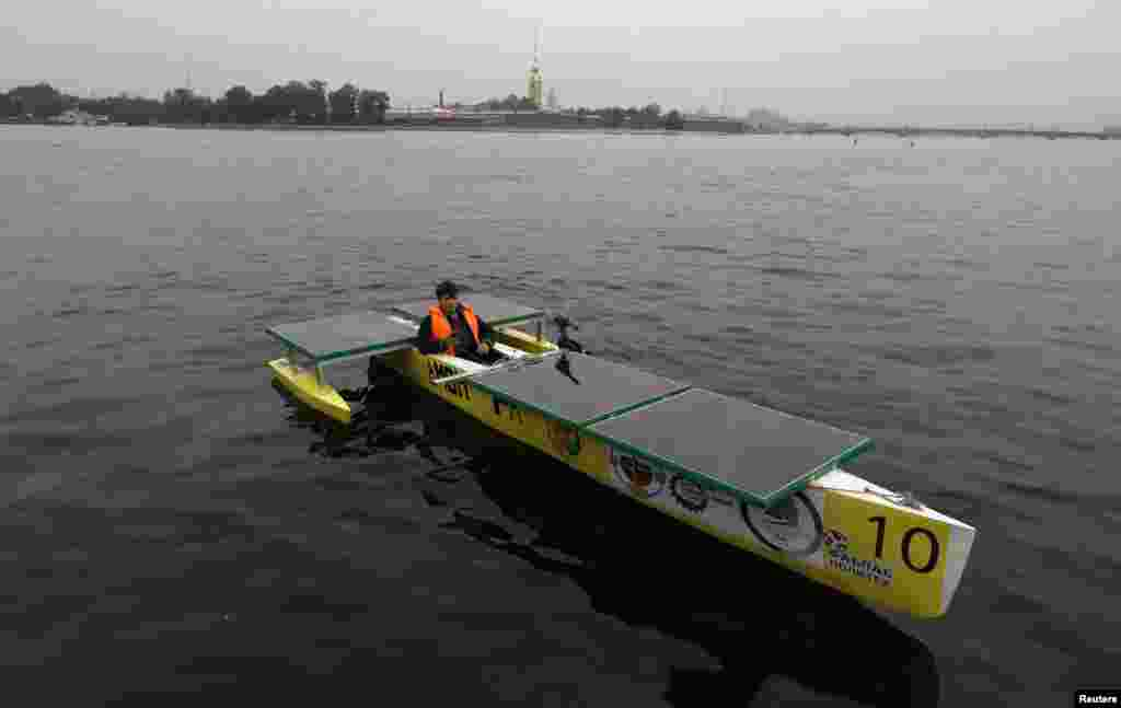 "Russian designer Aleksei Maistro on board his electro-solar boat ""Amon Ra"" in St. Petersburg. The boat is expected to participate in an international competition of solar boats in 2015 in the Russian city. (Reuters/Aleksandr Demianchuk)"