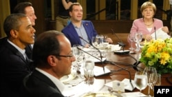 U.S. President Barack Obama (left) is joined by France's Francois Hollande (bottom), Britain's David Cameron (second left), Russia's Dmitry Medvedev (center), and Germany's Angela Merkel at a working dinner at Camp David on May 18.