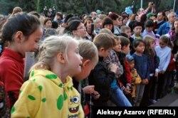 На площади перед казахским ТЮЗом во время открытия карнавала собралось много детворы. Алматы, 23 сентября 2012 года.