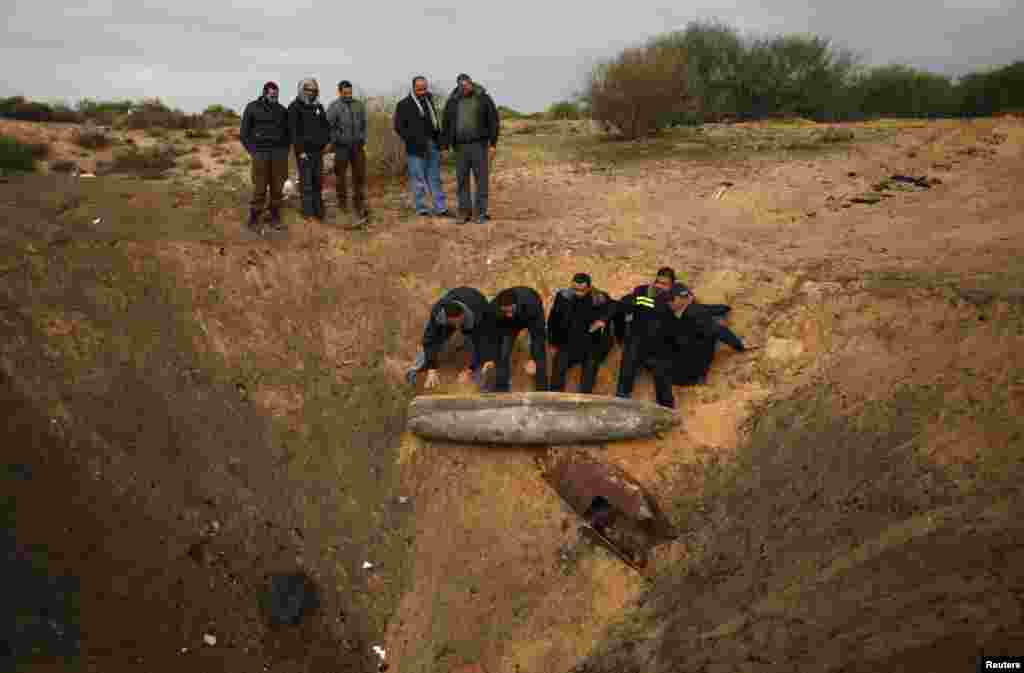 Members of Hamas security forces prepare to destroy a missile that witnesses said was fired by an Israeli plane during the eight-day conflict in the Gaza Strip. Eight days of Israeli air strikes on Gaza and crossborder Palestinian rocket attacks ended in an Egyptian-brokered truce agreement last month, calling on Israel to ease restrictions on the territory. (Reuters/Ibraheem Abu Mustafa)