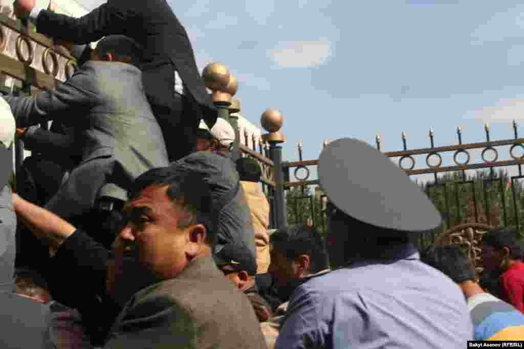Ташиев со своими сторонниками пытается пролезть через забор Белого Дома в Бишкеке.