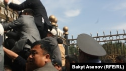 "Протестующие лезут через забор парламента во время митинга за национализацию рудника ""Кумтор"". Бишкек, 3 октября 2012 года."