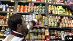 A vendor arranges canned products on a shelf at a grocery store in Tehran on December 19, as the Iranian government began to implement its controversial plan of scrapping subsidies on energy and food products as part of reforms that had been in the pipeli