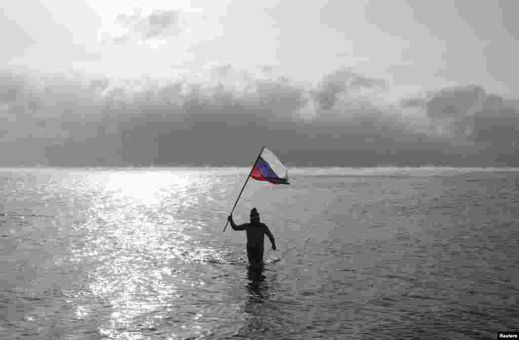 A man holds a Russian national flag while walking out of the Black Sea, as fans of winter swimming gathered on a beach on Orthodox Christmas in the Crimean port of Yevpatoriya. (Reuters/Pavel Rebrov)