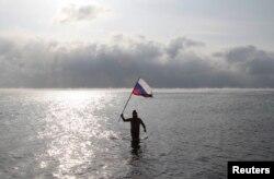 Мужчина с российским флагом в руках в Черном море, Евпатория