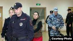 Полицейские заводят Гульчехру Бобокулову в зал суда.