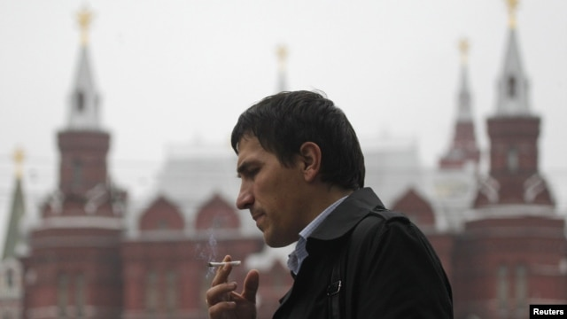 A man smokes on a street in central Moscow