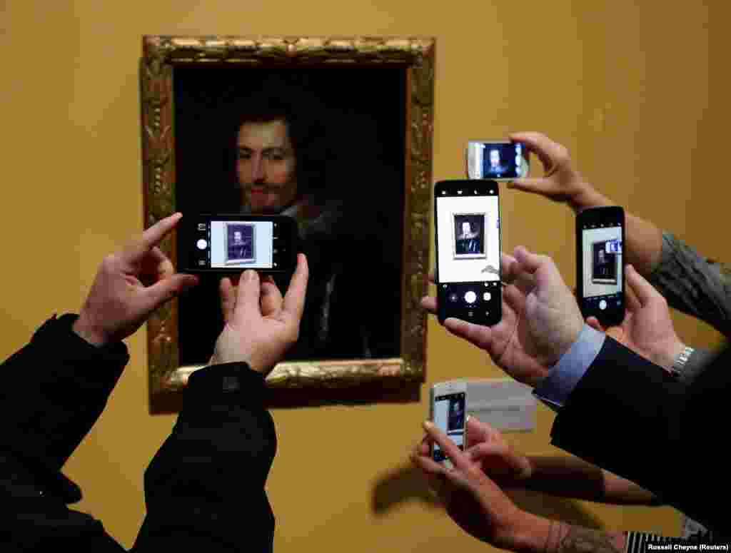People take pictures on their mobile phones of the lost Rubens masterpiece George Villiers, which is on show at the Kelvingrove Museum, Glasgow, Scotland. (Reuters/Russell Cheyne)