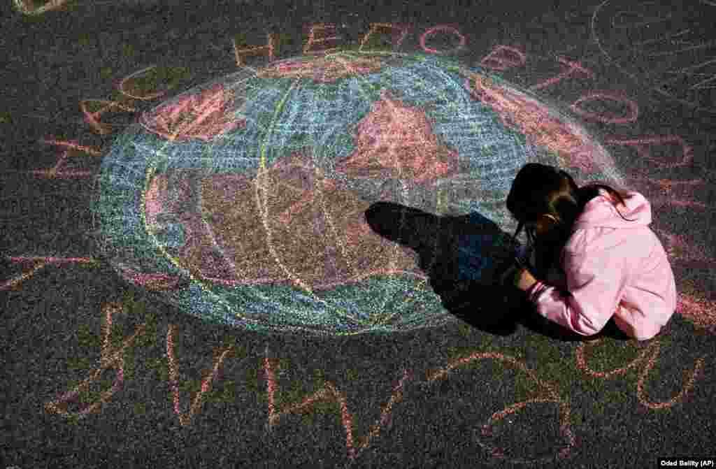 Дитина допомагає намалювати крейдою Землю під час громадського екологічного проєкту в міжнародний День Землі в Києві, 22 квітня 2006 року