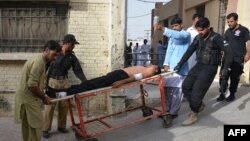 Pakistani policemen carry an injured colleague at a hospital following a bomb explosion in Quetta in September.